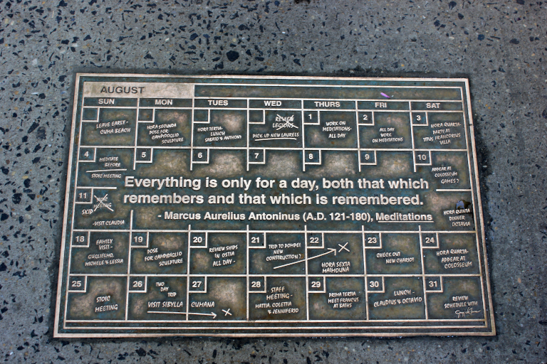 A plaque set in a sidewalk. A quote from Marcus Aurelius.